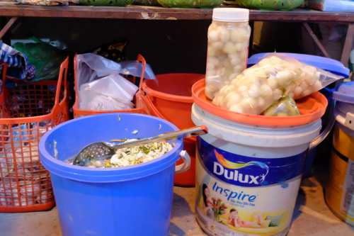 Fresh dưa chua at a street stall, sold next to fermented garlic and figs
